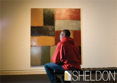 Student sitting looking at art in the Sheldon